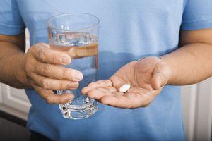 мужчина держит таблетку